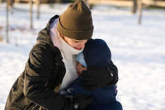 Mother and son in the snow. A mother hugging her two year old son in the snow Stock Photos