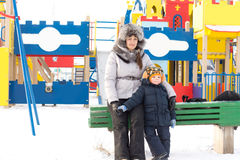 Mother and son in a snowy childrens playground Royalty Free Stock Photo