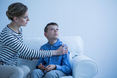 Mother and son on the sofa. Mother and her autistic son sitting on the sofa Royalty Free Stock Images