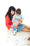 Mother and son spending time together. They sitting on floor with books and pencils near them and reading from a book,check also in this collection series Stock Images