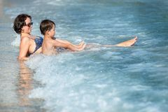 Mother and son splashing in ocean waves Royalty Free Stock Image