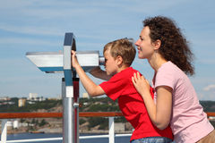 Mother and son stand on deck of ship. Boy looks through binoculars at landscape; focus on woman Stock Photo