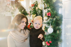 Mother and son standing near the Christmas decorations. And smiling royalty free stock photos