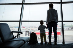 Mother and son standing near window in airport Stock Photography