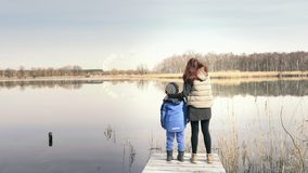Mother and son are standing on pier at beautiful pond. Mother and son are standing on small wooden pier at beautiful pond and enjoying countryside. Red-haired stock footage