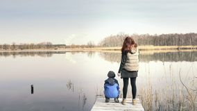 Mother and son are standing on pier at beautiful pond. Mother and son are standing on small wooden pier at beautiful pond and enjoying countryside. Red-haired stock video