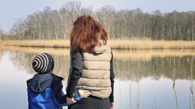 Mother and son are standing on pier at beautiful pond. Woman and small boy are standing on small wooden pier at beautiful pond and enjoying countryside. Red stock footage