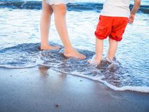 Mother and son standing on seashore. Mother and son in red shorts (lower half only) standing on the seashore with feet in the waters of the incoming tide Stock Photos