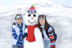 Mother and son (7-9) standing by snowman in snow, smiling, portrait, mountain range in background Royalty Free Stock Images