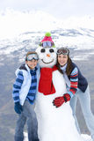 Mother and son (7-9) standing by snowman in snow, smiling, portrait, mountain range in background Royalty Free Stock Image