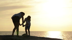 Mother and son stay on the outcrop overlooking the sea at sunset and laugh stock video