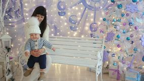 Mother and son in the studio Christmas sitting on the bench stock video footage
