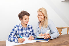 Mother and son studying. A boy is doing his homework and his mother is helping him with it. They look very happy Royalty Free Stock Photos