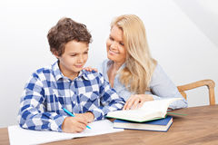 Mother and son studying. A boy is doing his homework and his mother is helping him with it. They look very happy Stock Image