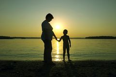 Mother, son and  summer sunset. Family and sunset on the beach Royalty Free Stock Photos