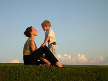 Mother with son on sundown. Green grass blue sky with clouds royalty free stock photos