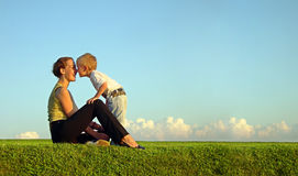 Mother with son on sundown. Kiss by nose. long royalty free stock photo