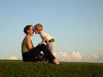 Mother with son on sundown kiss by nose. Clouds on horizon royalty free stock photo