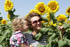 Mother with son among sunflowers Stock Photo