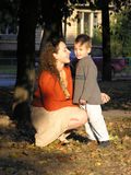 Mother with son. sunset. Mother with son on autumn leaves at sunset light stock images