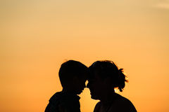 Mother and son at sunset beach Stock Images