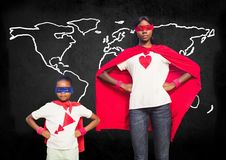 Mother and son in superhero costumes standing against world map in backround Stock Photos