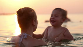 Mother and son swim in the sea Stock Photos