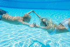 Mother and son swim underwater. Holding hands in the pool stock images