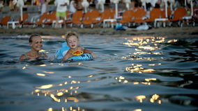 Mother and son swimming in the evening stock video footage