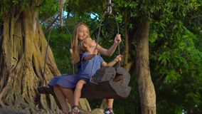 Mother and son swing on an exotic old swings hanging on a big tropical tree in a tropical park. Travel with kids concept.  stock video