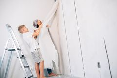 Mother and son take off wallpapers together and prepare room for Stock Photography