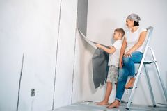 Mother and son take off wallpapers from wall and prepare room fo. R renovation Stock Images