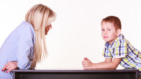 Mother and son talk and argue sit at table. Stock Photography