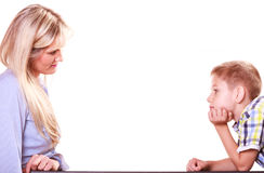 Mother and son talk and argue sit at table. Royalty Free Stock Photos