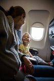 Mother and son talking and laughing on board of plane Royalty Free Stock Images