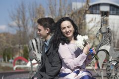 Mother and son are together. Couple sitting on a banch in the park stock image