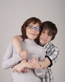 Mother and son are together and smile. In studio stock photos