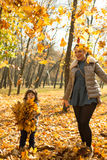 Mother and son tossing leaves Royalty Free Stock Photo