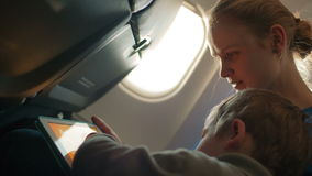 Mother and son with touchpad in the plane