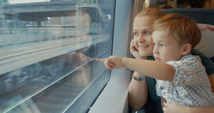 Mother and son traveling across the city by train. Young mother traveling with little son by train. They looking out the window while riding across the city. Mom stock video