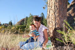 Mother and son under a big pine tree. Mother and son goofing under a big pine tree in afternoon sun Royalty Free Stock Images