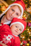 Mother and son under Christmas tree Stock Images