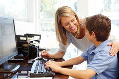 Mother and son using computer at home Royalty Free Stock Photo