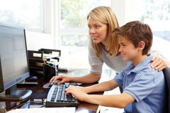Mother and son using computer at home royalty free stock images