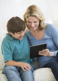 Mother And Son Using Digital Tablet Together At Home Stock Images