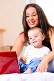 Mother and son are using laptop. At home Stock Photo