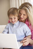 Mother And Son Using Laptop At Home Stock Images