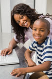 Mother and son using laptop. In the kitchen stock photo