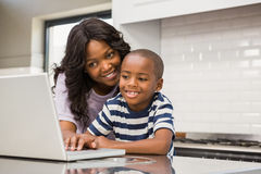 Mother and son using laptop. In the kitchen stock images