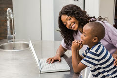 Mother and son using laptop. In the kitchen royalty free stock photography